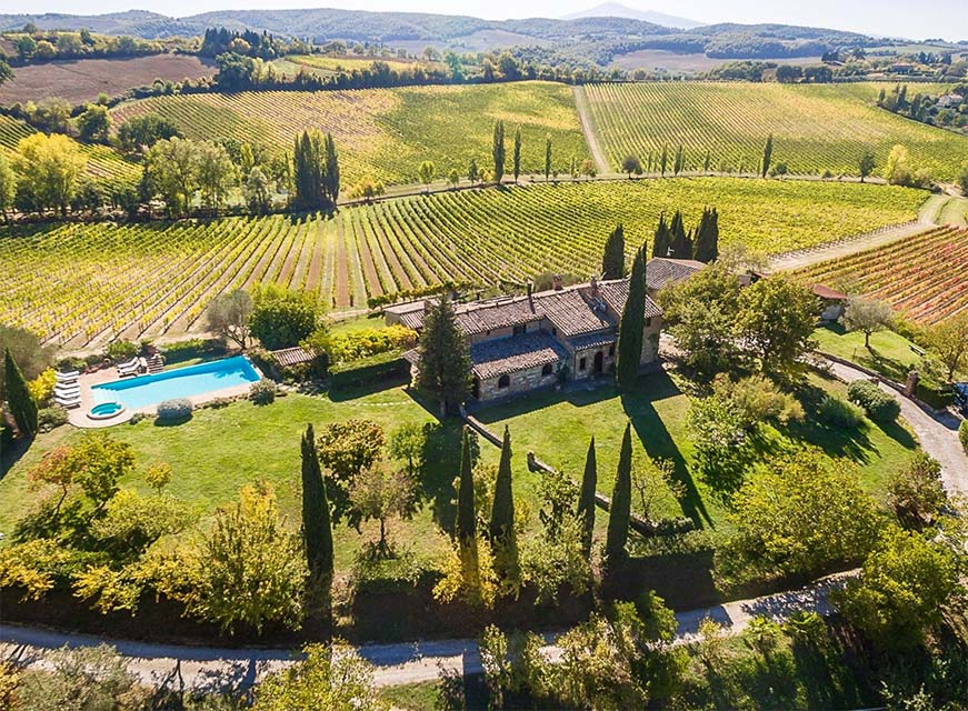 Farm in Tuscany Italy in the sunshine with fields to be harvested